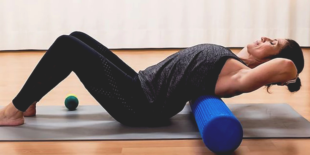 Woman Exercising with Foam Roller on Yoga Mat by Organic Newsroom