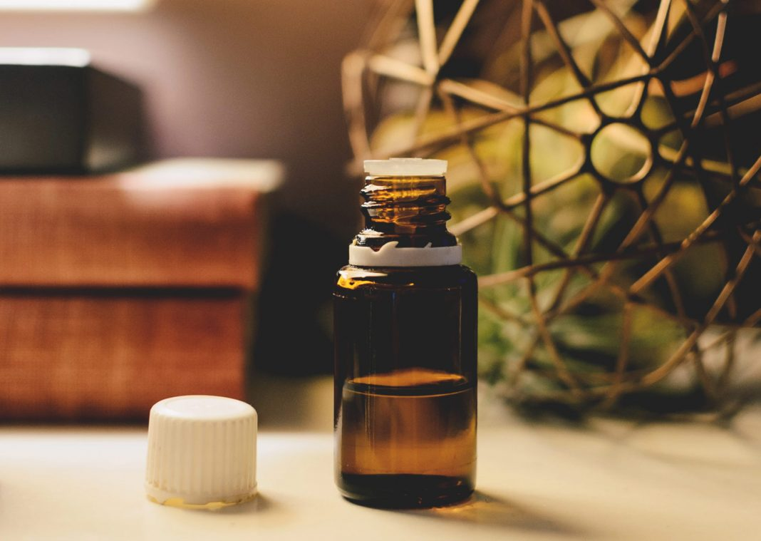 essential oil aromatherapy bottle and herbs